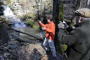 Burgess Carey, left, showed neighbor Bill Meade a natural waterfall feeding spring water into Boone Creek in 2011. Photo by Tom Eblen